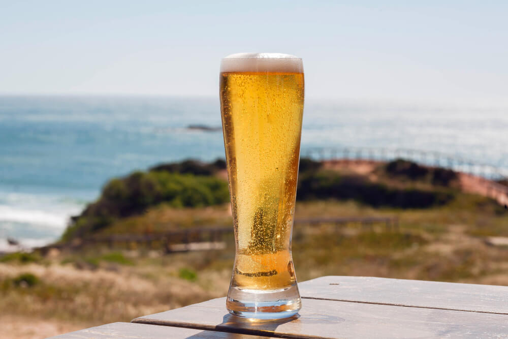 Photo of a Tall Pilsner at an Oregon Coast Brewery with the Sea in the Background.